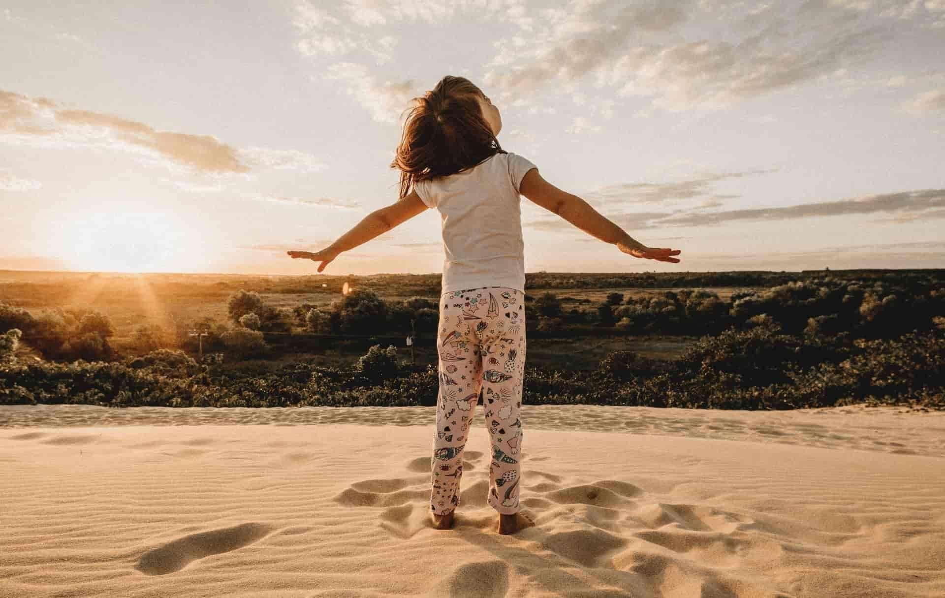 Une petite fille avec les bras écartés pieds nus dans le sable