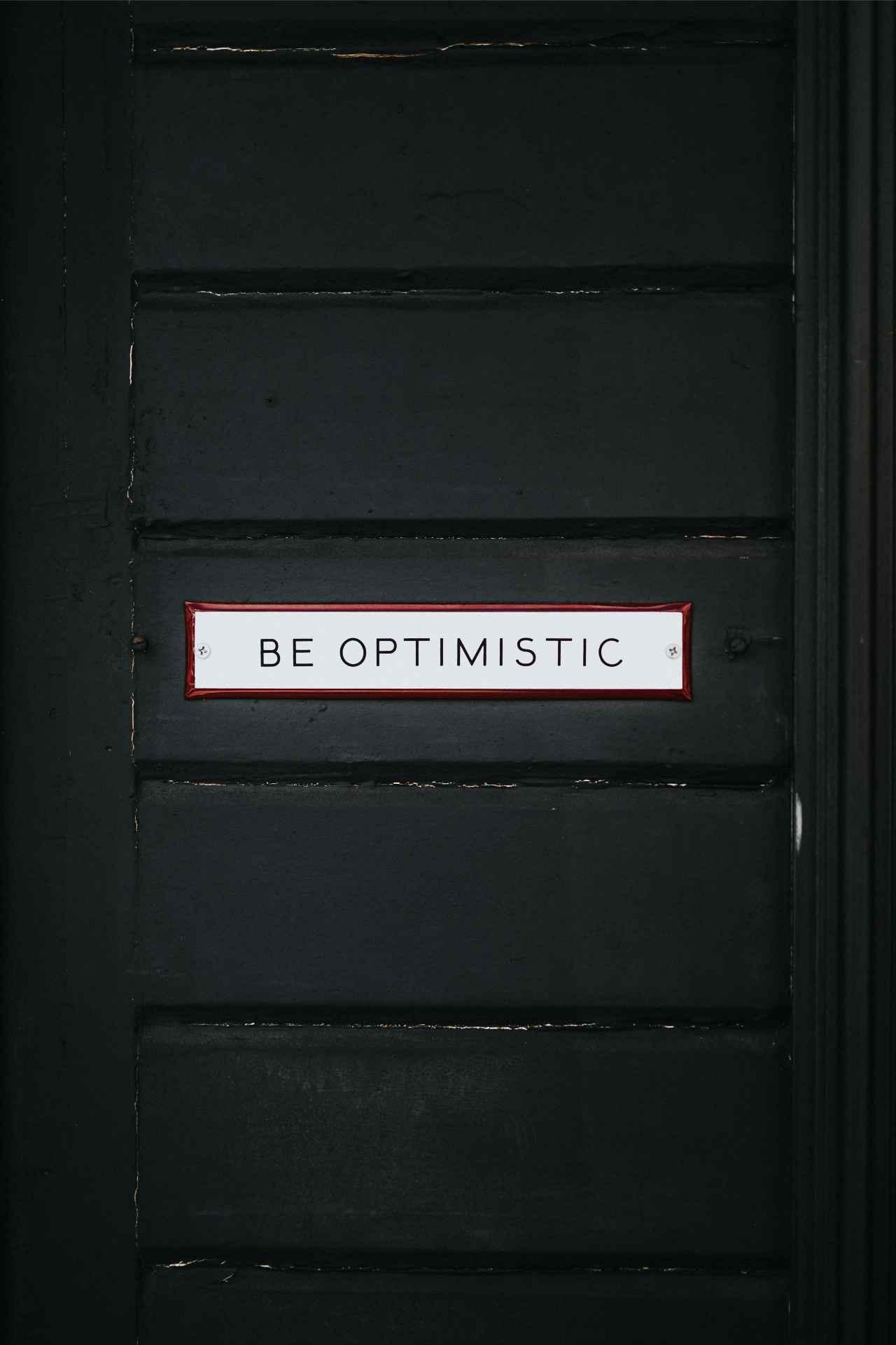 """Une porte avec un écriteau """"être optimiste"""""""