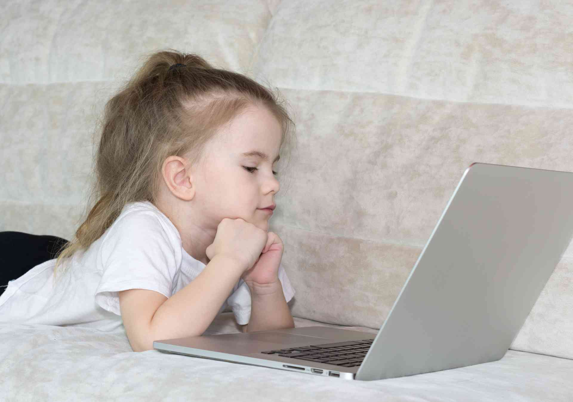 Une petite fille devant un ordinateur portable