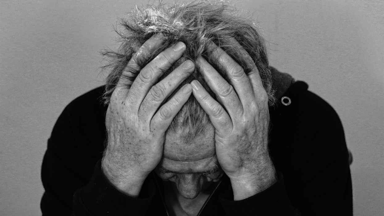 Un homme souffre et se tient la tête