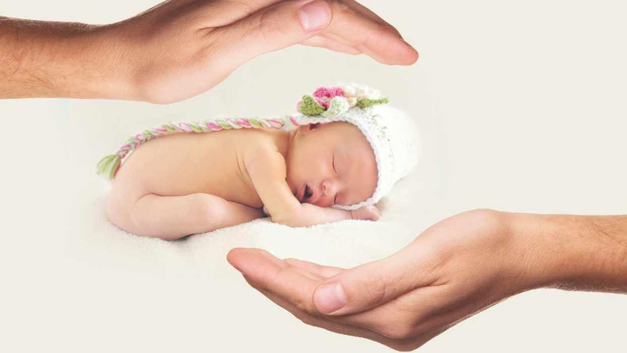 Un enfant prématuré avec un bonnet entre des mains